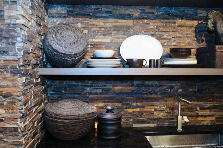 rice baskets, dishes and antiques on open oak shelves mounted on a jagged stone wall