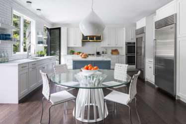 Highly functional kitchen features painted custom cabinetry by Bilotta, white Neolith Classtone countertops and a white subway tile backsplash as a backdrop for bold accents.