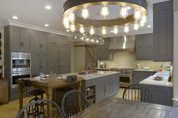 "Country kitchen with grey cabinets, double ovens and a 48"" professional range."