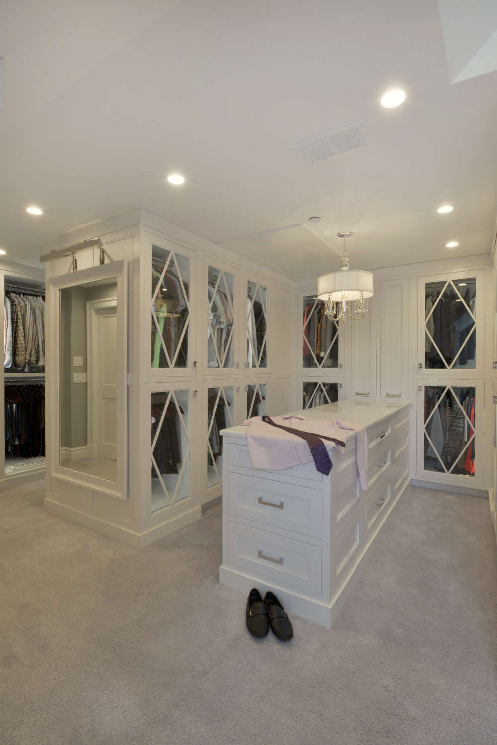 Expansive, walk-in closet outfitted with white painted custom Bilotta cabinetry with glass doors featuring decorative mullions and a marble-topped island with drawers for additional storage.