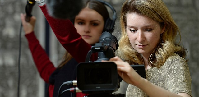 Two students recording using a video camera and boom microphone