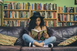 woman reading a book on a sofa with bookshelves behind her