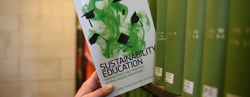 hand taking book off shelf with title sustainability education