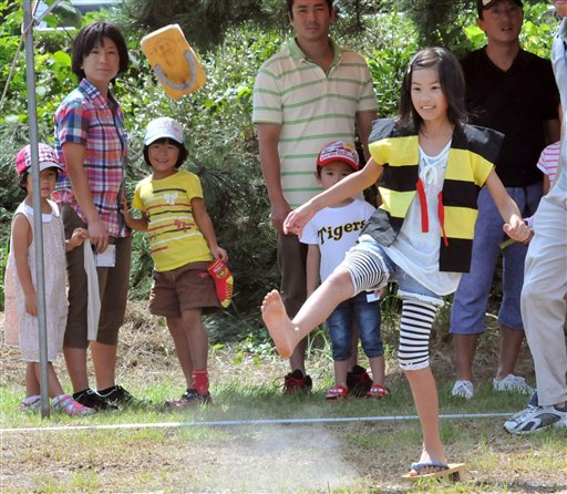 """Girl competes in """"geta"""" sandal toss competition"""