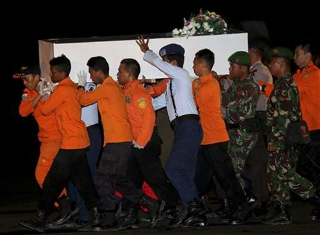 Members of the National Search And Rescue Agency carry a coffin containing the body of one of the victims on board the ill-fated AirAsia Flight 8501 to transfer to Surabaya at the airport in Pangkalan Bun, Indonesia, Thursday, Jan. 1, 2015. Searchers were racing
