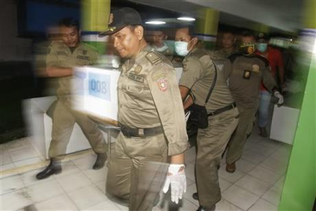 Local security officers carry a coffin containing a body of a victim of AirAsia Flight 8501 at the main hospital in Pangkalan Bun, Thursday, Jan. 1, 2015. Searchers were racing