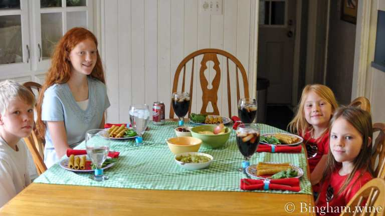 Four children seated at dinner table.