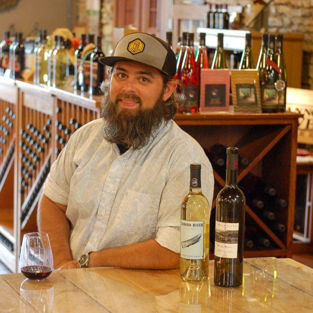 Sam Jennings posed with wine bottles.