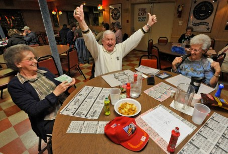 """Bingo, Rosedale, MD -- 2011 -- Bill James, 80, of Rosedale, center, celebrates after winning $95 in a """"full card"""" game, as his wife Mary James, 76, left, and friend Thelma Sutphin, 68, of Middle River, look on, at VFW Post 6506. The VFW Post wanted to hold casino nights with card games and roulette to raise more money, if the legislature approved an expansion of gambling. (Amy Davis / Baltimore Sun)"""