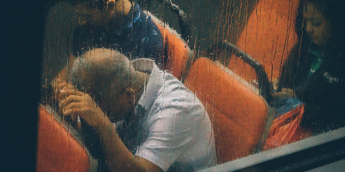 Exhausted man slumps over the seat in front of him in a bus, while the rain runs down the window.