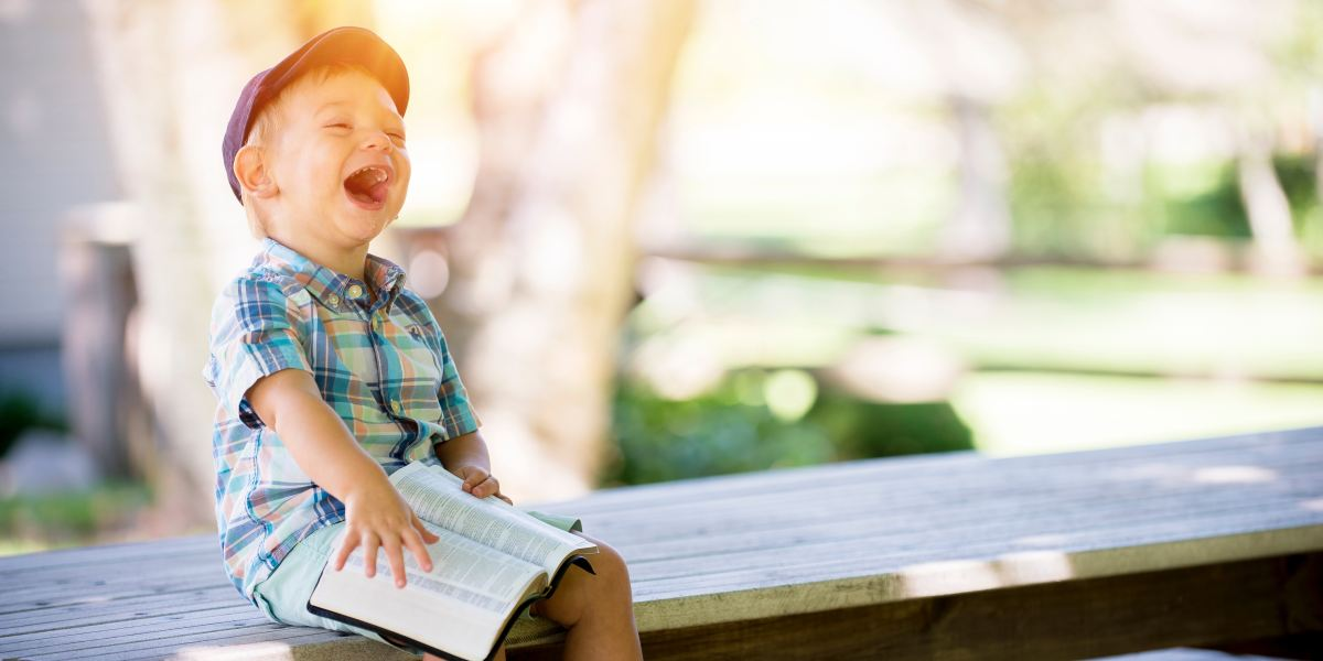 Boy laughing joyously with a book