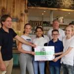 Personeel van de BioExpress reikt de prijs uit aan Team Sushi-burger
