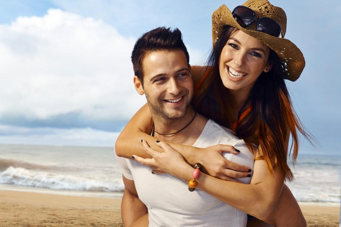 Happy loving couple having fun on the beach, enjoying summer hol
