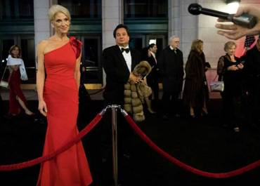 Kellyanne Conway answering to press while her husband George Conway stands behind her.