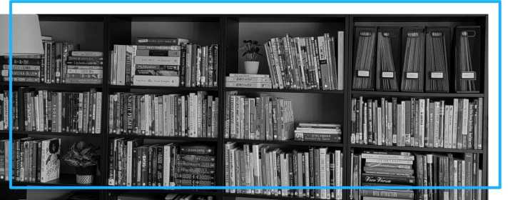 A black and white photo of 4 tall bookshelves filled with books.