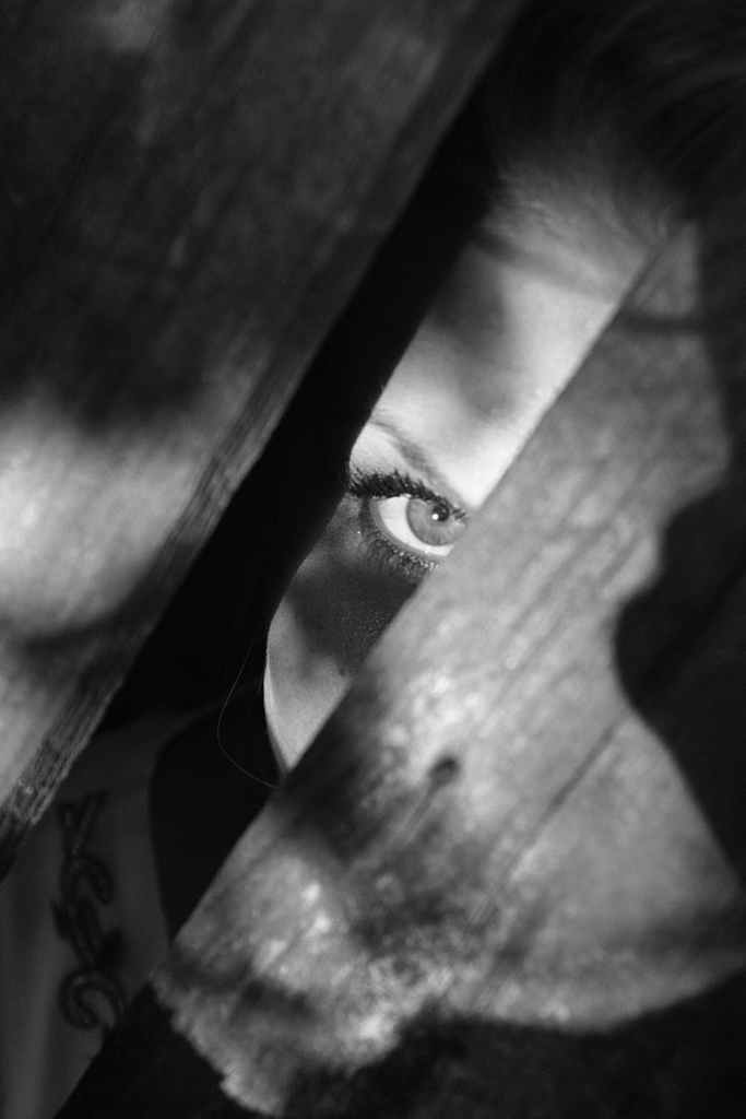 picture of woman hiding behind broken fence and peering out
