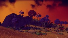 A hilly landscape spilling with dim light during the night. (Image credit to Birb Friends, retrieved from No Man's Sky using PlayStation Share)