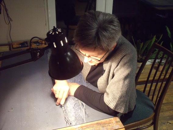 Daliute Ivanauskaite cutting linoleum in her studio