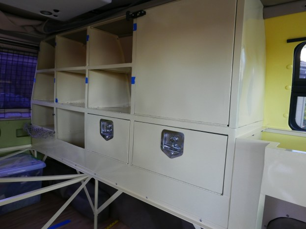 The cabinets with lock boxes that run along the bed