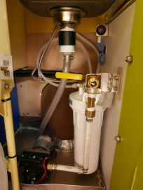Plumbing and water filtration system. The sink drains out the van and the pressured part of the plumbing all sits in a drain pan in case of leaks that also drains out the van. The shower hose hooks up to the yellow lever.