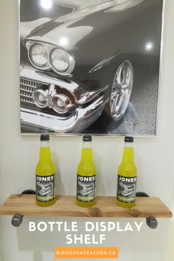 Upcycle soda bottles into an industrial bottle display shelf. The vingnette uses black pipe fittings to create the shelf that holds the bottles. Birds of a Feather | Storage | pipe shelf | pipe shelves | jones soda | soda bottles |pop bottle display #pipeshelves #storage #jonessoda #sodabottles #displayshelf