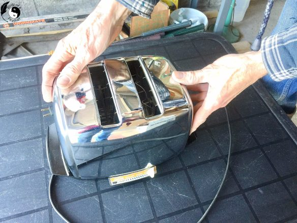 Hands on toaster about to be taken apart for spray paint chrome project