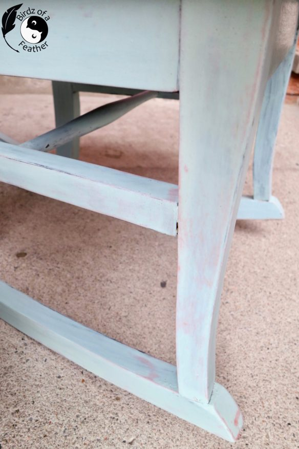 "When we found this painted rocking chair, it happened to be on a day with hit the jackpot of curb side chairs. You might remember this chair we found on the same day. A little fabric refresh was all it needed. On the other hand, our little rocker is getting the full monty! It will still be a painted rocking chair. But we're milk painting and stencilling it. Then we're protecting the hole shebang with hemp oil. But don't worry, she'll be just as charming, if not more so, when we're through! Before we get into painting and stencilling, don't forget to get your craft mojo on at Birdz of a Feather and subscribe! You can also follow us on Pinterest, Facebook, YouTube and Instagram. Using Milk Paint on a Painted Rocking Chair My eyes went immediately to that gorgeous blue colour in the middle of the pack when I came across this new line of Milk Paint by Fusion. At that moment, I had to have Amalfi Coast for my little rocker. Milk Paint by Fusion doesn't officially launch until sometime in October (don't quote me on that), but the proprietor let me buy one of the sample packs on display. Prep Work for Painted Rocking Chair With a creative direction for the chair behind me, Hubs got to work sanding the old paint finish on our rocker with 220 grit sandpaper. Underneath the wooden seat we discovered it used to have caning! I wiped away the dust with a damp rag. Keep going over until it no longer picks up any dust. After that, we had some repair work to do. Making Repairs to a Painted Rocking Chair One of the dowels in the stretcher was completely broken. You could take every piece apart just to replace the dowel, but there's an easier and faster way. If you ever run into the same situation, check out this post on how to fix a broken chair leg. Time to paint! (By the way, not all the links in our posts are affiliate links, but we love sharing where you can buy the products we use regardless. However, when you click on the bold Amazon or Old Sign Stencils affiliate links below, we may receive a small commission for referring qualifying purchases. If you purchase a product through those links, you don't pay a cent more! Thank you for helping to support our little blog). Materials for Painted Rocking Chair Wooster 2"" ShortCut Angle Paint Brush Adjustable height work table Funky Junk Old Sign Stencils - Grain Sack Stripe Milk Paint By Fusion Accent paint (we use PPG Break Through) Jar Measuring spoons Water Craft sticks for mixing. You can also use a mini wisk for mixing). 320 grit sand paper (this is for sanding the milk paint. We also used 220 grit for the initial sanding of the chair. Foam dauber Bristle paint brush (for getting into details) Hemp oil Mixing Milk Paint by Fusion Grab your favourite paint brush and gather your materials. I tend to only mix in small batches what I can comfortably use in the time I have to paint. Since the chair is small, I use a measuring spoon to measure quantities. Mix the milk paint in a glass jar - equal parts powder and water. Stir with a craft stick or mini wisk. The advantage of using a wooden craft stick to mix is that you have record of the paint colour when you're done because the milk paint will stain it as you stir! Pop on the lid and shake the jar. Then let it sit for 15 minutes to half an hour so the milk paint powder is fully absorbed. Don't have a jar? Check out my best 'no mess' idea for how to mix milk paint! I would've used that mixing method for this project too, but wanted to switch it up. I used my mini wisk, instead of the craft stick, to mix the last batch! Stir Milk Paint Occasionally After mixing, but before using the milk paint, be sure stir up up again. Occasionally during use, remember to give it another stir. The powder tends to settle as the paint sits. I only hit the highlights of the wood carving with the tip of my brush because I want the black to show through in the recesses. For the remainder of the back slat, I only paint the sides and back leaving the face the original black paint. As you'll see later, I have something special planned for the slat. The black background is a jumping off point for a stencil I'm going to add. Everything else gets 3 light coats of milk paint. One thing to keep in mind with lighter colours of milk paint: you will need more coats than usual. I barely squeaked by with the 50g package. For that reason, next time I milk paint a chair with a light colour, I'll buy a larger quantity! Grain Sack Stripe Stencil As pretty as the milk paint is, a little red 'lipstick' will catapult this chair makeover over the top. So I'm embellishing the slat of the chair with this Grain Sack Stripe Stencil from Funky Junk's Old Sign Stencils. You can check out Funky Junk's full line of Old Sign Stencils here*. * Funky Junk Old Sign Stencils has generously provided us with a complimentary stencil. Of course, all opinions are my own. How to Prevent Paint Bleed Under Stencil See those narrow pin stripes along the edges of the grain sack stencil stencil above? Those can be tricky to paint. There are six tricks I use to prevent bleed through under a grain sack stencil like this (or any stencil, for that matter). 1. Prep Surface Before applying the stencil to the back slat, first prep your surface with 220 grit sandpaper so it's completely smooth. There should be no rough texture or uneveness that would cause the stencil to 'float' above any areas along the edge. 2. Let gravity be your friend Instead of keeping my chair upright and applying the stencil in a vertical position, I lay it down on an adjustable height work table so it's horizontal instead. Because of that, It's much easier to work on (it'll help save your back too, once the table is adjusted to the perfect height). The fact of the matter is that curved rockers will still cause the chair to incline (as you see below). That incline happens to give us a much better vantage point to photograph and film. But feel free to raise the lower end of the rocking chair, if you prefer to put something underneath, so it's perfectly horizontal. 3. Lie Stencil Flat Whenever a piece I'm working on has an uneven surface, like the raised portions at the top and bottom of the slat, I'll tape down my stencil at a point where I can lie it as flat as possible. For instance, notice that the bottom edge of the stencil is even with the bottom edge of the slat. If I line up the bottom edge of the stripe with the bottom edge of the slat instead, that will result in a gap, which is what you don't want. You can always fill in the missing portion of the stripe by taping the edges with painters tape. 4. Use Painters Tape Once the grain sack stripe stencil is positioned on the slat, tape it down with painters tape. Notice that in the middle the tape goes right through the narrow stripes on the side. That will help hold it down. When all other parts are complete, just lift those two pieces of tape and finish painting those areas. 5. Keep the Pressure On I use my fingers to apply pressure to the edges of the stencil where I'm painting. Then I diligently move along to the next spot keeping consistent pressure. You'll see that more clearly in the video. 6. Dry Applicator The last trick I use to get a great result is to make sure the applicator is dry before painting. I dab the paint applicator onto papers towels to offload most of the paint before stencilling. Easy does it: apply a few light coats instead of a heavy one and you'll get crisp, clean lines. I happen to love these foam daubers for applying paint to stencils. You can also find mini daubers you can wear on your finger to get into tighter spaces - like the pinstripe. There are lots of conventional and unconventional options you can use to apply paint to a stencil. I've even had success with sponge makeup applicators. Try a variety of different applicators to develop your own preferences. Painting Around Carved Details on a Painted Rocking Chair To get into the details like the carving at the top of the slat, stop stencilling at least an inch short of the carving. When you're happy with the density of the paint, carefully lift the stencil and set aside to dry. Apply some painters tape as shown to continue the stripe. I use a stiff bristle brush to get into the details (again make sure it's dry). Because the brush is stiff, it's easy to pounce toward the carving to fill in against the edges. Again, you'll see exactly what I mean in the video. Lift the tape and you're done. You'll notice that the grain sack stripe still stops short of the bottom. No, I didn't get lazy. I was going to fill it in as I did with the other end - and even had it taped, but Hubs really likes it this way.  I think it's quirky. Besides, every once in a while I let Hubs think he actually gets to have some input into the design of our pieces 😉. In all likelihood, it won't get seen anyway; I'm planning on making a chair cushion in a future post! Sand the Newly Painted Rocking Chair Once all the painting is complete, I lightly sand the milk paint with 320 grit sandpaper to knock back any rough spots. This is optional, but I also 'wet sand' the hemp oil in the next step too. While you're sanding a piece that still has it's original paint, feel free to distress the edges in a few spots so the original colour shows through. I love seeing some of the original black finish peeking through, but it's totally up to you. Seal Painted Rocking Chair with Hemp Oil Hemp oil is an all natural product that, if applied like I'm doing here, will make your milk paint finish feel silky smooth. You can use a natural bristle brush to apply hemp oil or a cotton rag (I'm using a rag). I also wear a glove because it can get messy working with oil. My favourite hemp oil is this one by Homestead House. Pour a little into a container, dip the rag, then spread the oil onto the surface. There's no need to wipe in the same direction as the grain. Then take a clean piece of 320 grit sand paper and rub it through the oil on the surface to burnish the milk paint. Use a microfibre cloth to wipe away any excess oil.  How Often Do You Have to Apply Hemp Oil? I think on a small piece of furniture like this chair, you can probably get away with reapplying the hemp oil every three years or so. It really depends on the use and also how dry the environment is. How Long Does Hemp Oil Take to Cure? Hemp oil will fully cure in a month. Check on the piece every week and if you notice any 'spots' showing up in the finish, that's just excess oil that the piece won't absorb. Wipe it with a clean microfibre cloth, then check back again up until it's cured. Will Hemp Oil Change the Colour of My Paint? Yes and no! It will deepen slightly and make the colour pop. Notice how much richer the chair seat looks against the surrounding milk paint that hasn't been oiled. However, the next day after applying the hemp oil, I did get red bleed through that you see below. Funnily enough, I actually love how that random effect looks because of the red grain sack stripe on the back slat. It like it was meant to be! I reuse original hardware whenever I can. These tacks help cover the hole in the seat left after the removal of the caning. Antique Rocker Reveal Just as I was about to take a photo, a little red autumn leaf blew into the shot. I think that must be Mother Nature's way of thanking us for saving this little charmer from a certain fate in the landfill! I added a chair pad we have kicking around just to show you that a cushion can make the rocking chair more comfortable and inviting. Are you into the plaid this autumn? Or maybe you prefer a crisper look sans the seat cushion? We've had so much fun upcycling our recent chair bonanza. I don't know much about this particular little vintage rocking chair. But I do know that it really rocks now, in more ways than one! I assume it's for a child or it could be a nursing chair; women were a lot shorter back in the day. If you know anything about the origins of this sweet rocker, please leave us a comment! Subscribe and Pin If you enjoyed our painted rocking chair project, please pin. Pinning is always welcome and appreciated :). Interested in more painted furniture projects? Check out our Paint Techniques category to browse our DIYs."