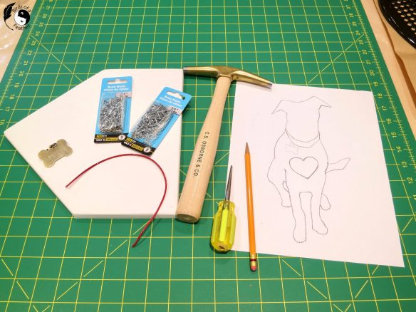 Just like a real dog, this DIY string art dog tugs at the heart strings! Supplied shown are brad nails, hammer, wood board, awl, wire (optional) pencil and string art template