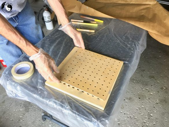 Pegboard positioned over small paint jig for spray painting