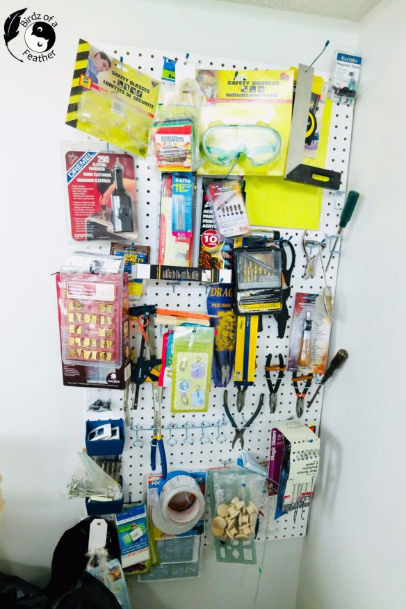 Traditional wall mounted pegboard craft organizer loaded up with craft supplies and tools