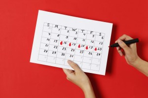 The girl notes on the calendar the days of menstruation on a red background.