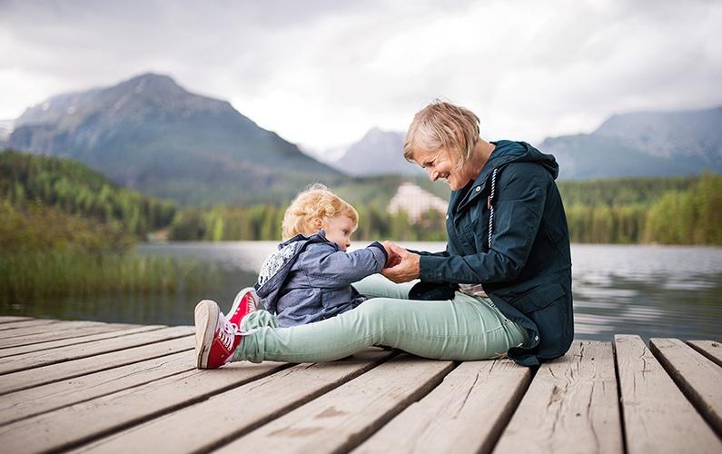 grandma-and-granddaughter-sitting-lakeside