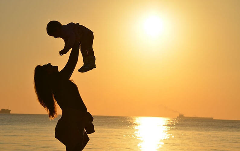 silhouette of mom and baby at beach