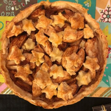 photo of whole apple pie with cutout stars on top