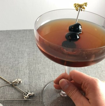 Photo of a Manhattan Cocktail in a coupe glass with three cherries for garnish on a cocktail pick with a gold horse on top.