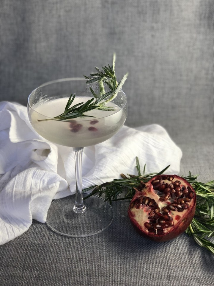 Rosemary Gin Gimlet in a clear coupe glass on a gray linen background with a half a pomegranate to one side and a sprig of rosemary in the drink for ganrish.