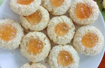 Pineapple coconut thumbprint cookies AKA pina colada cookies; coconut thumbprint cookies coated with extra coconuts and filled with pineapple jam.