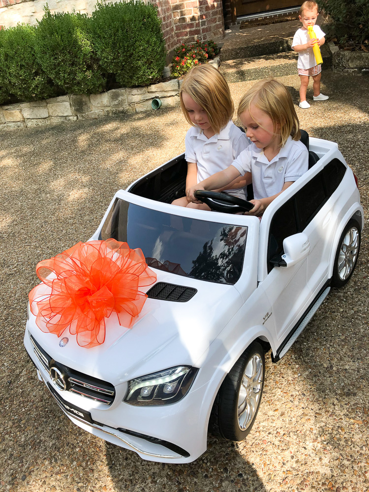 two toddler boys in white drive in car