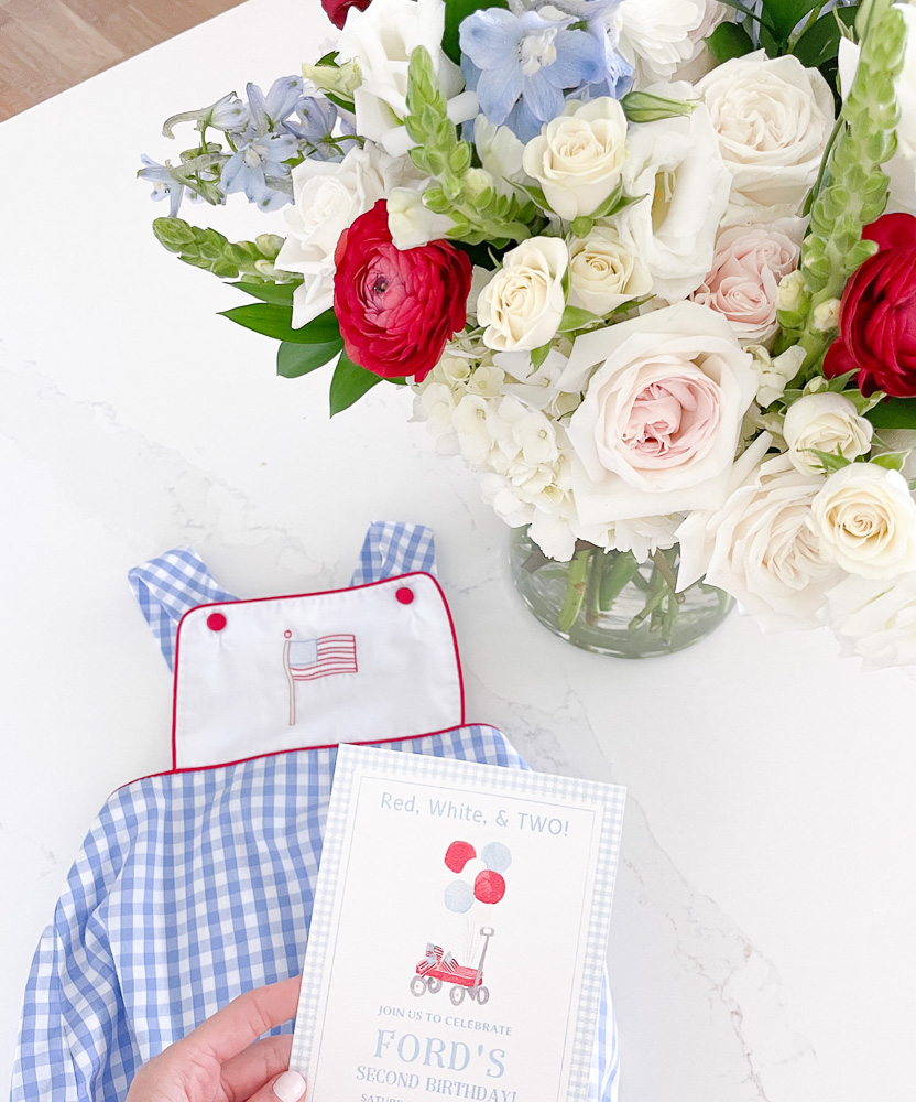 flower arrangement baby boy outfit and invitation