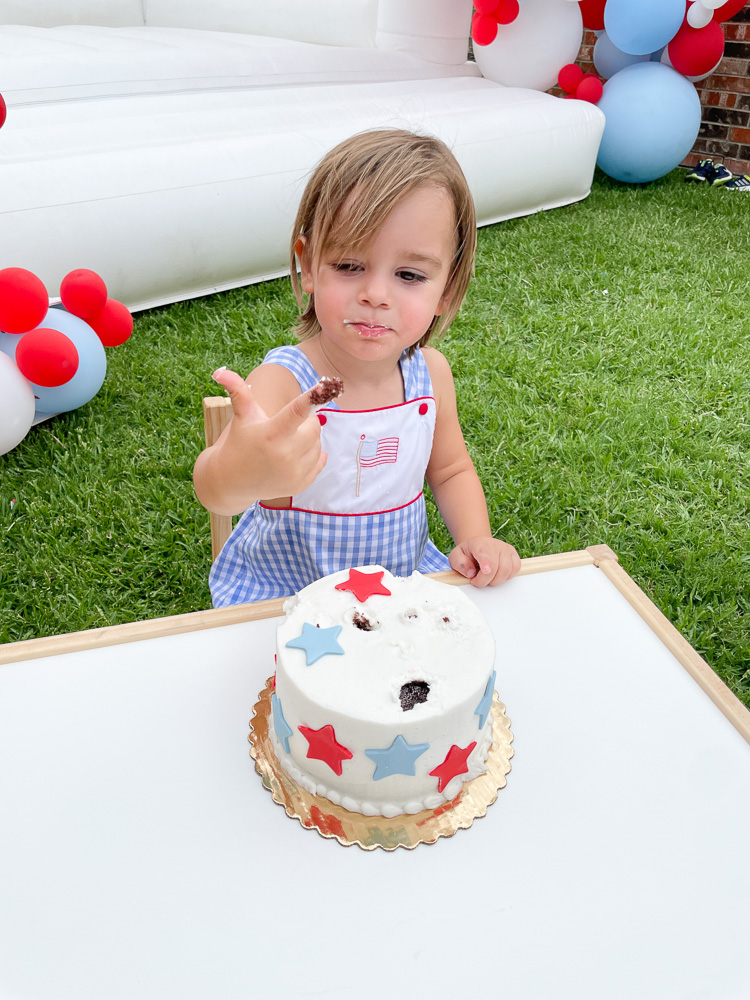 toddler boy digging into birthday cake with fingers