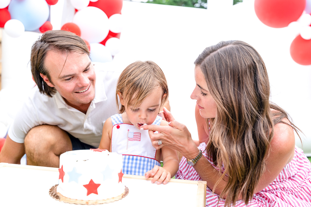 mom and dad with toddler feeding birthday cake