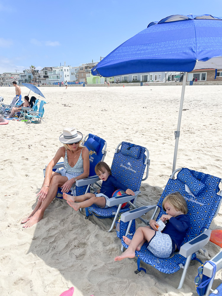 woman with two little boys sitting in beach chairs at the beach
