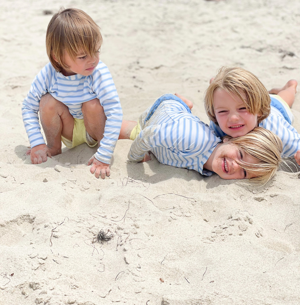 three little boys playing in the sand at the beach
