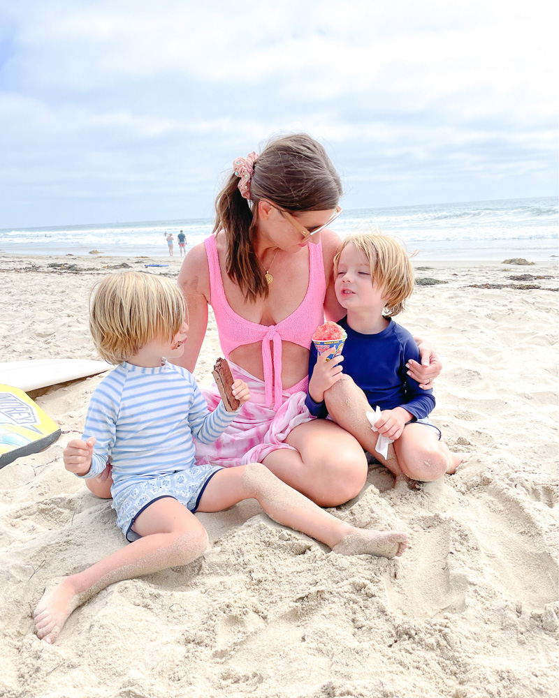 mom with two little boys sitting in sand beach