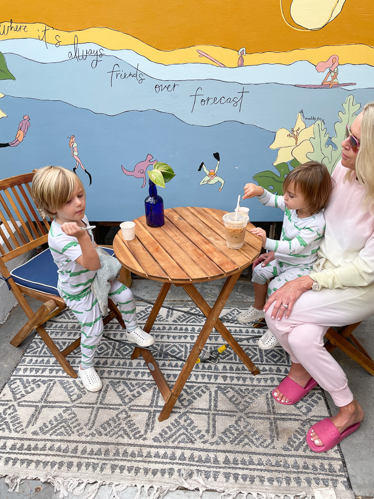 woman sitting at an outdoor cafe with two little boys
