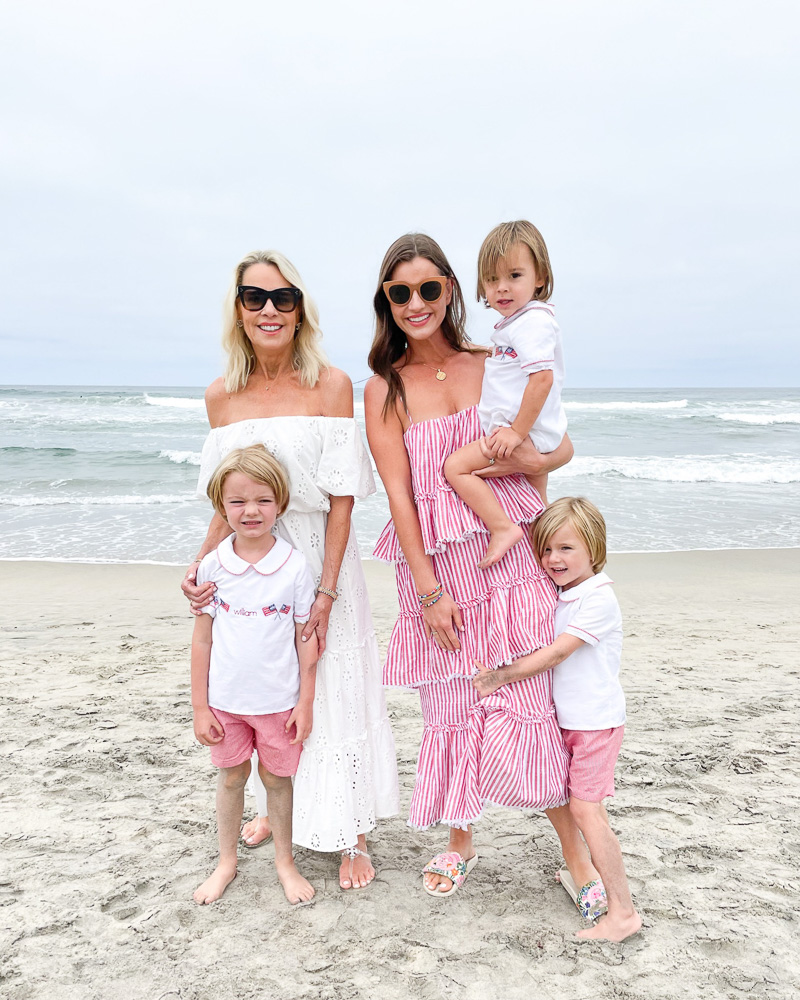 two women with three little boys standing at the beach