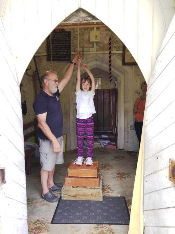 Giles teaching Martha the art of Bell Ringing.