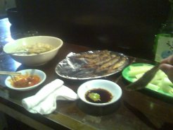 Grilled fish, a spicy soup, some vegetables, spicy sauce and soju.