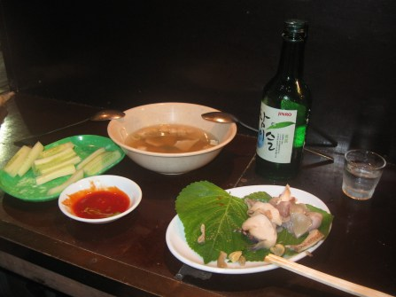 Dinner on the streets of Seoul. Fresh seafood, spicy sauce, some vegetables, a spicy soup and soju (Korean liquor).