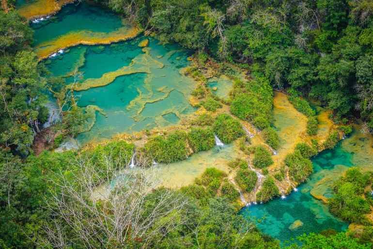 Aerial/drone view of Laquan Guatemala waterfall with turquoise waters bordered with green forest on either side in post about tips for affordable luxury travel